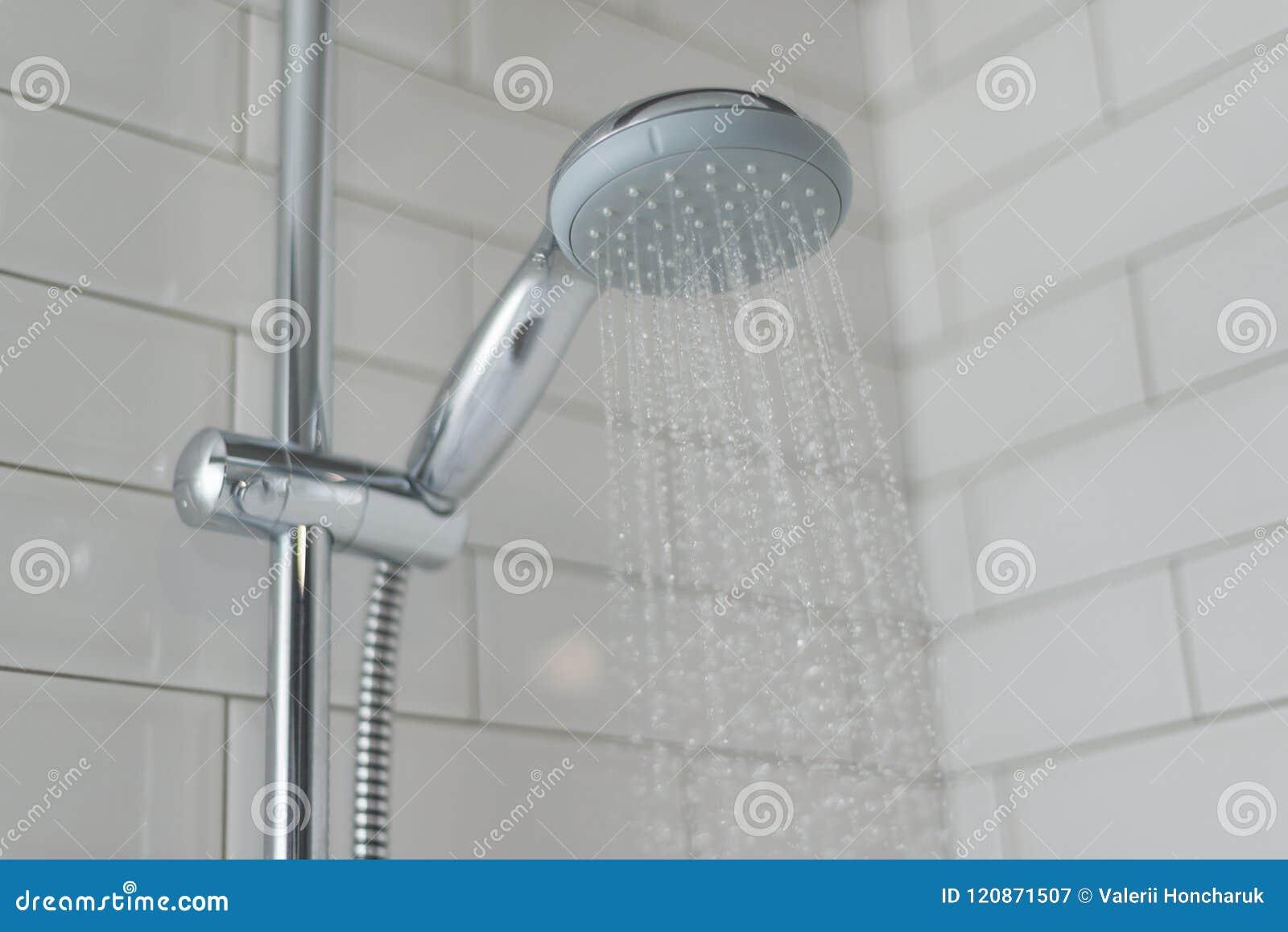Primo piano della doccia del cromo rubinetto nelle piastrelle di