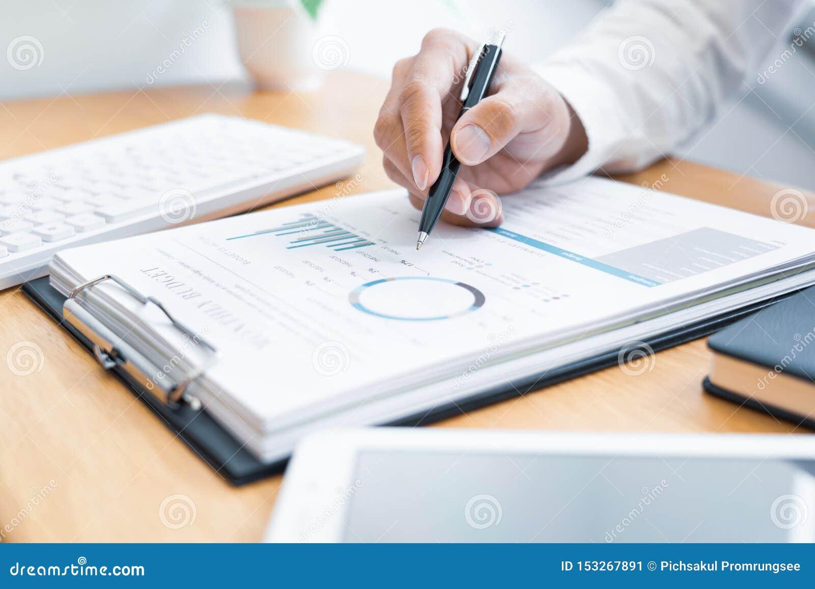 Primo piano della lettura e della scrittura dell uomo d affari delle mani con il contratto di firma della penna sopra il document