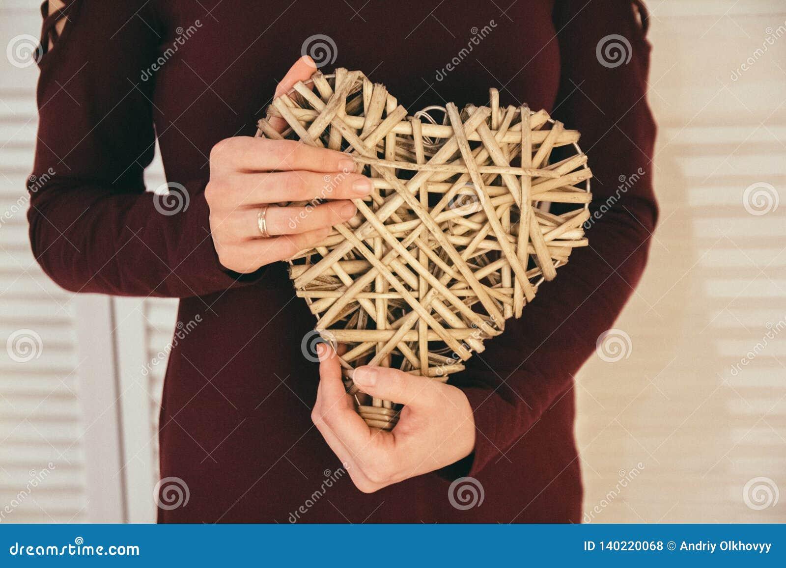 Primo piano della manifestazione fatta a mano del ricordo di cuore-forma dalle mani della donna Il simbolo di amore per sempre a