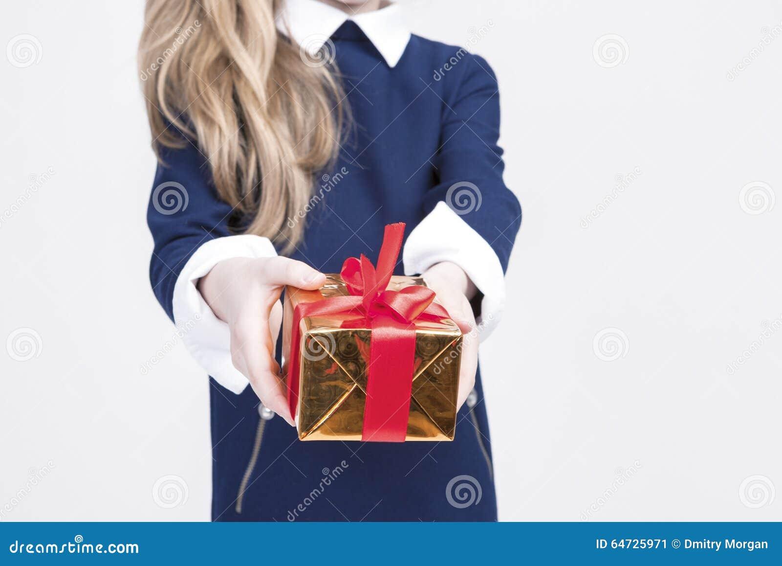 Primo piano della mano di piccola ragazza bionda che dà il contenitore di regalo di Natale