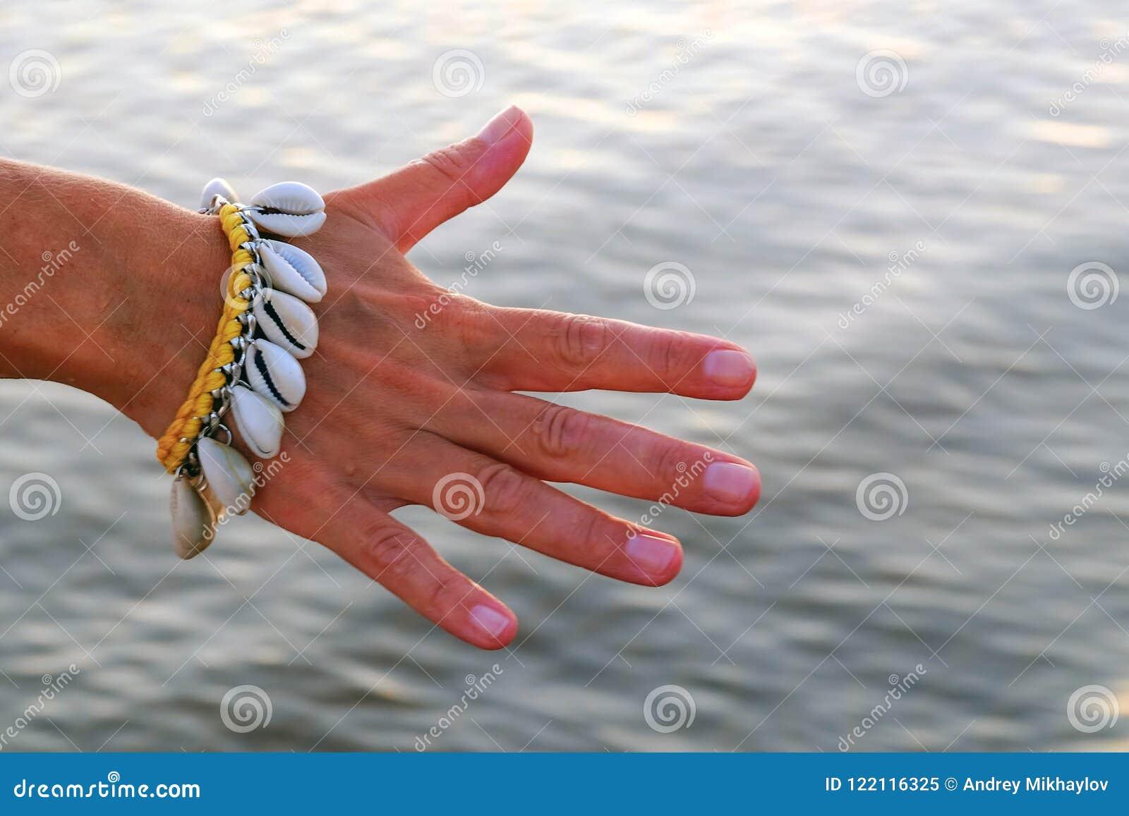 Primo piano della mano di una ragazza delicata con un braccialetto fatto delle conchiglie sui precedenti di acqua