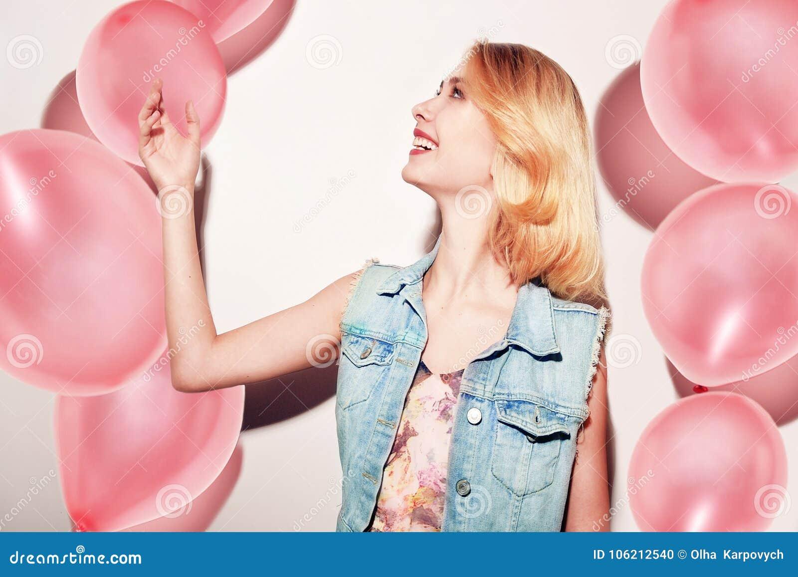 Primo piano della ragazza bionda sveglia che sta in uno studio, sorridente ampiamente e giocante con i palloni rosa Porta il vest