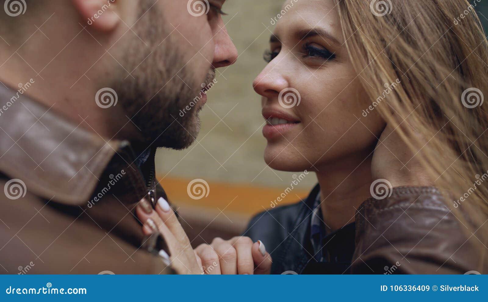 Primo piano delle coppie amorose felici che baciano e che abbracciano mentre passeggiata del havinhg in via della città