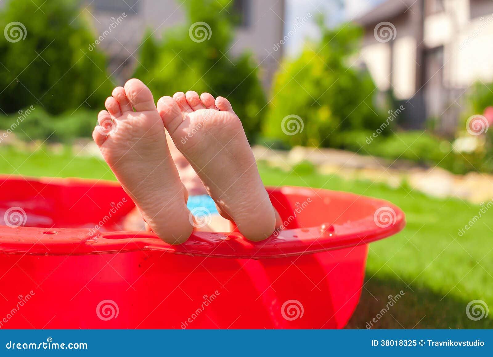Primo piano delle gambe del bambino in piccolo stagno for Piccolo stagno