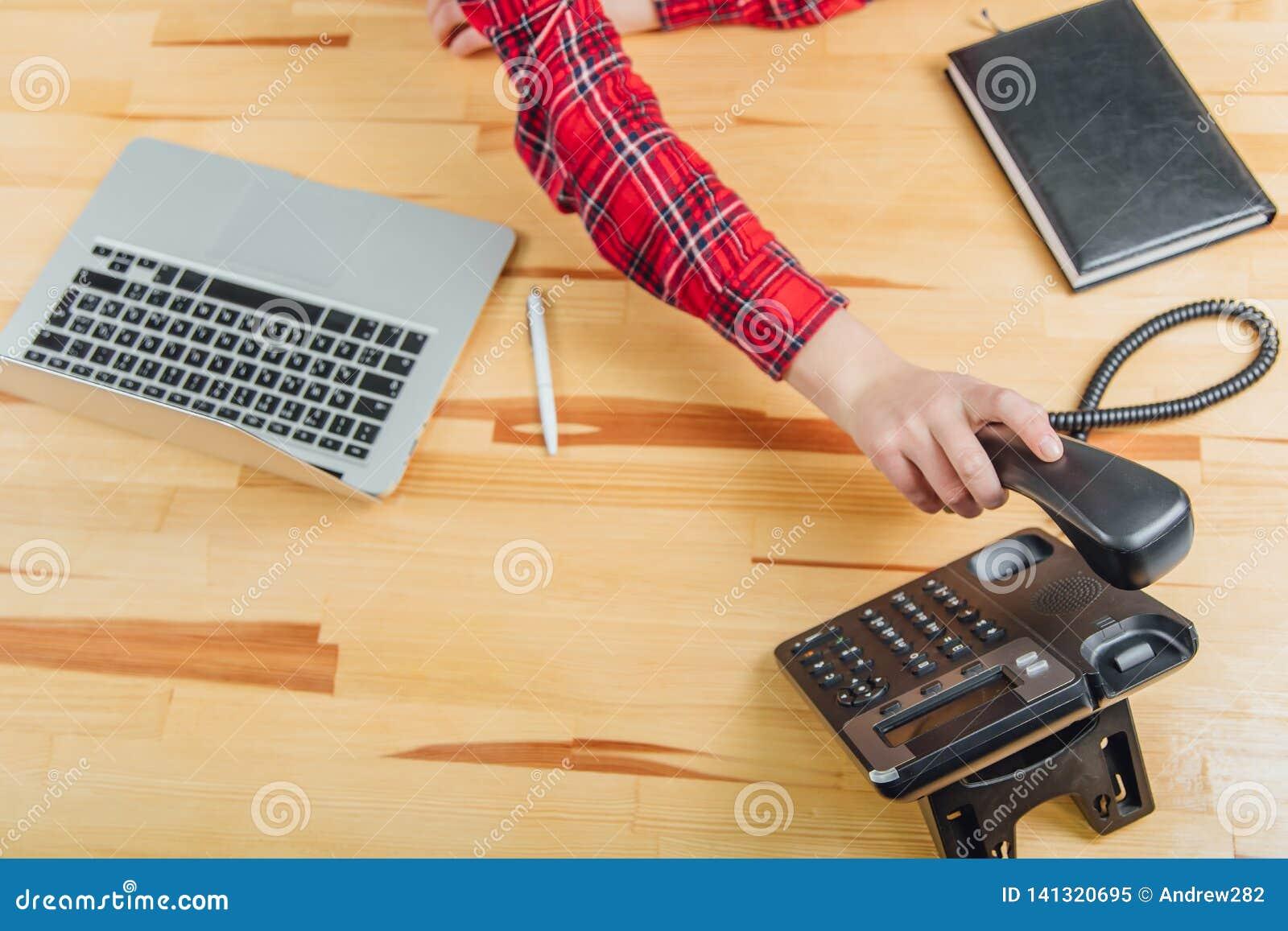 Primo piano delle mani delle donne in un ufficio con un telefono in loro mani che si trovano sulla tavola, posto di lavoro Contro