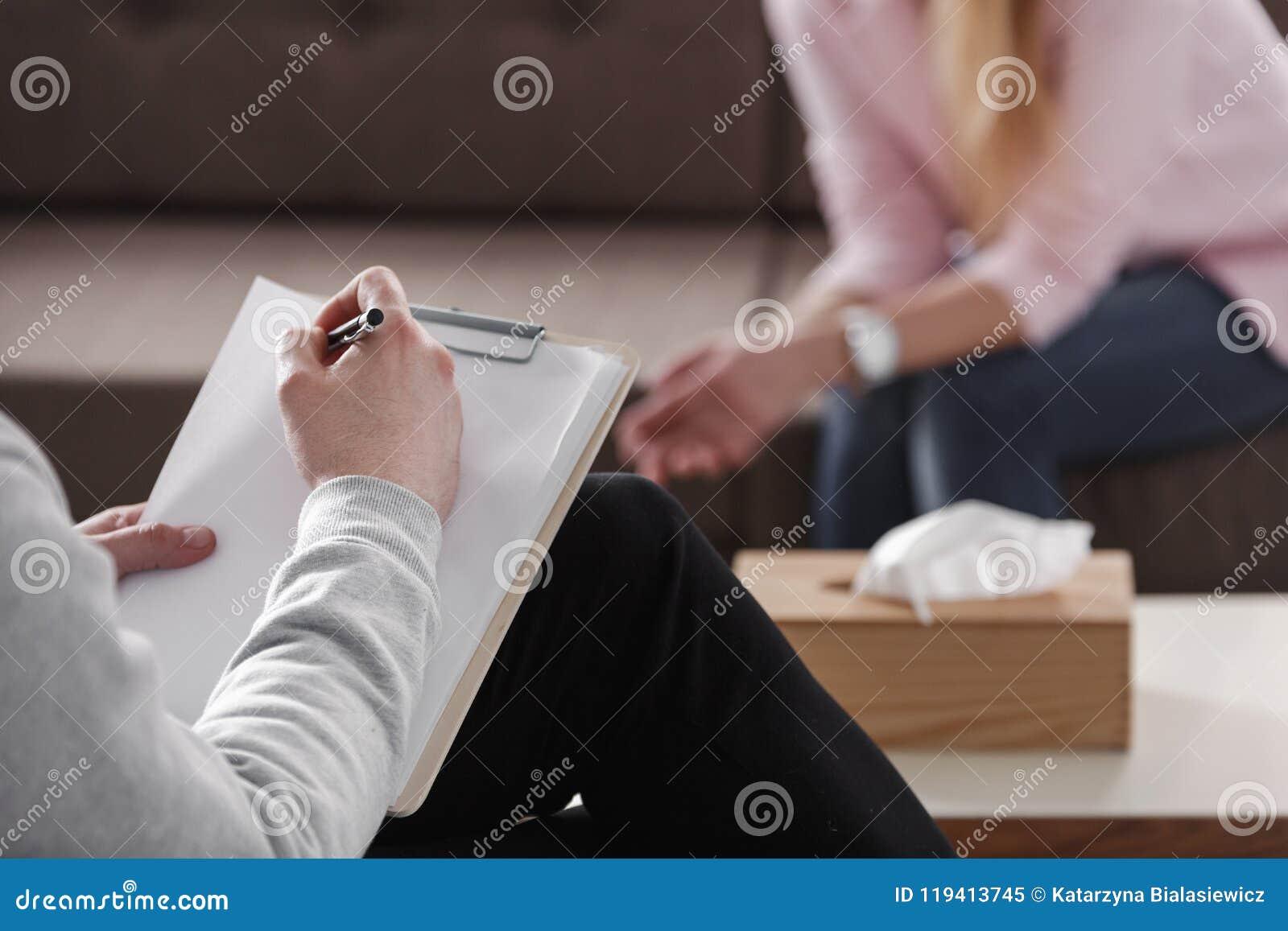 Primo piano delle note di scrittura della mano del terapista durante ses di consiglio