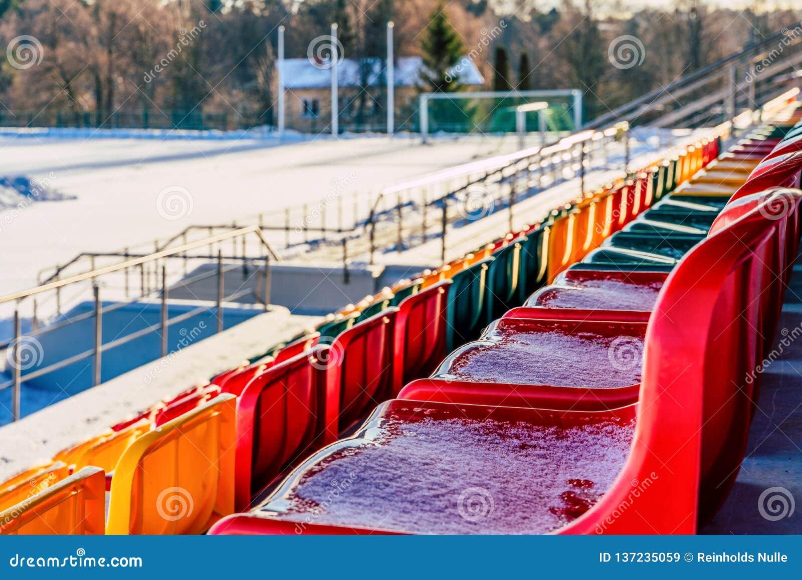 Primo piano di calcio variopinto vuoto & di x28; Soccer& x29; Sedili dello stadio nell inverno coperto in neve - Sunny Winter Day