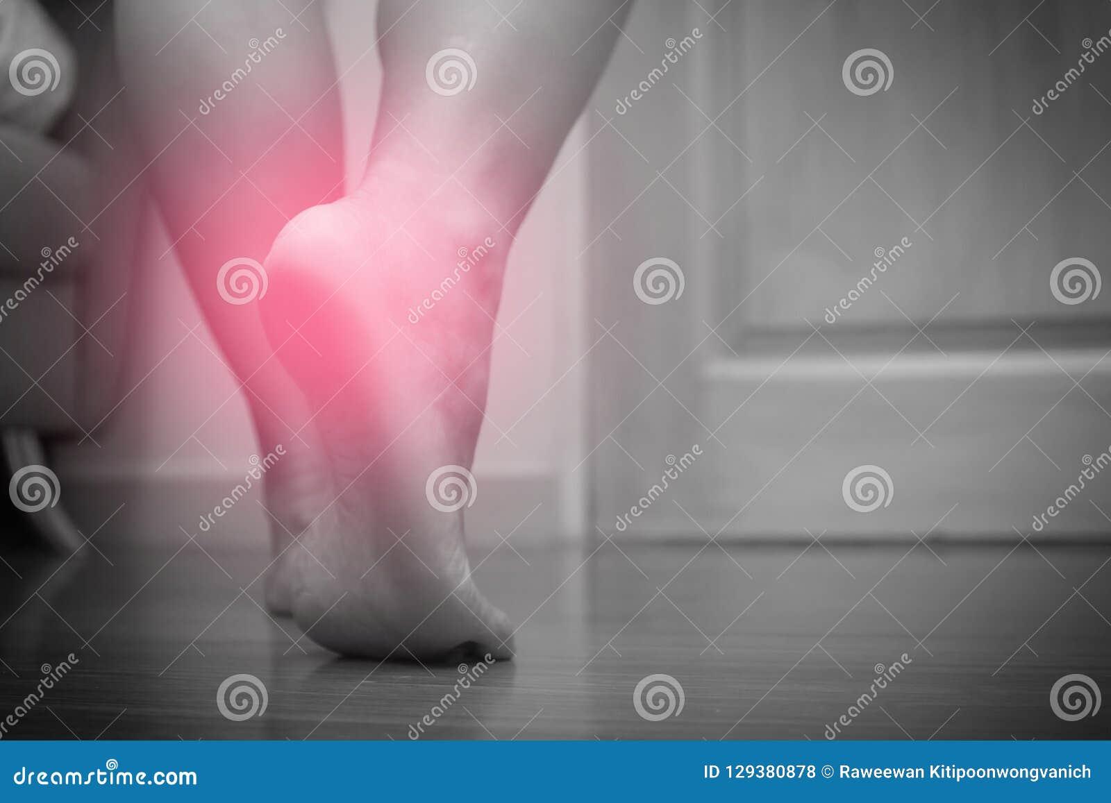Primo piano di dolore femminile del tallone del piede destro, con il punto rosso, fascite plantari Tono in bianco e nero