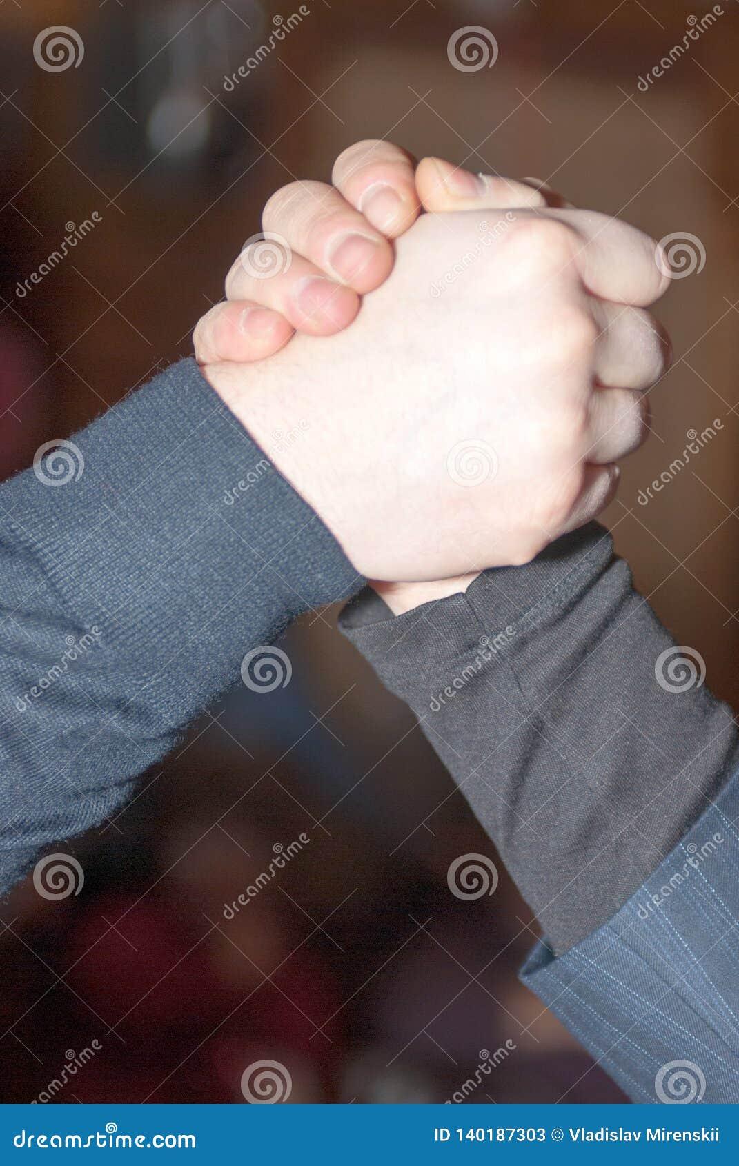 Primo piano di forte stretta di mano di due uomini in un collo alto ed in un vestito