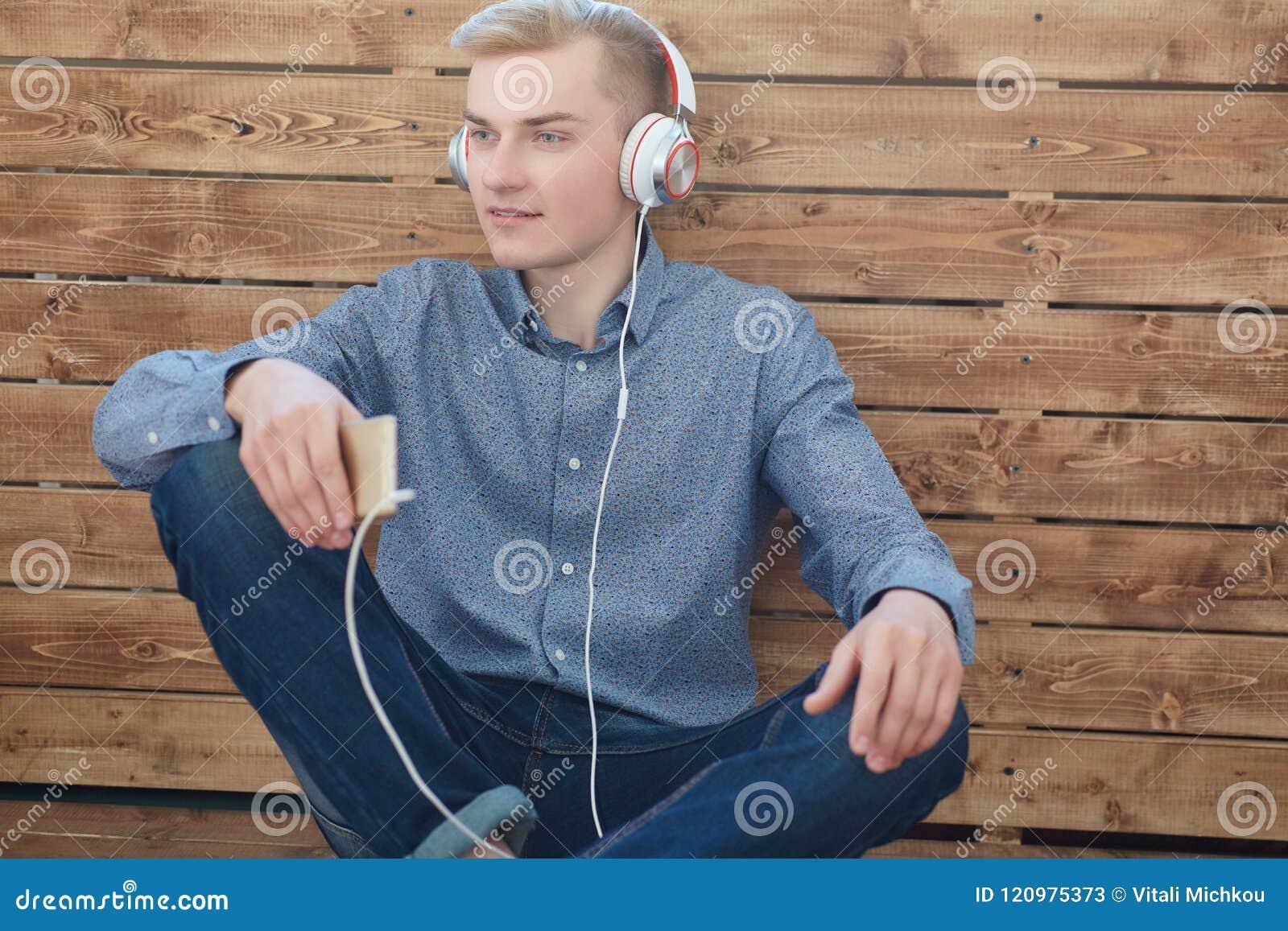Primo piano di giovane telefono cellulare scandinavo della tenuta dell uomo e di musica d ascolto con il sorriso mentre sedendosi