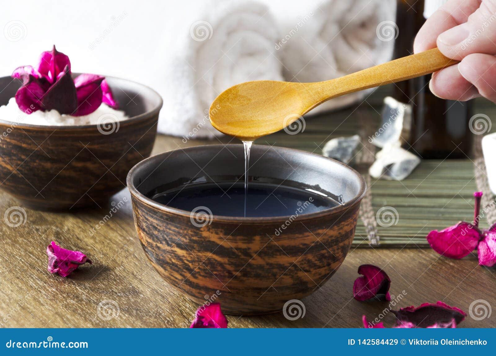Primo piano di olio per il massaggio nella ciotola ed in altri prodotti cosmetici Donna che prepara e che versa olio cosmetico pe