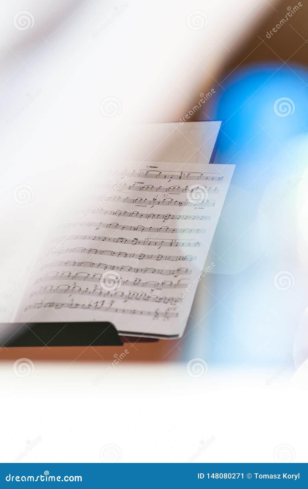 Primo piano di partitura nel fondo luminoso bianco con i chiarori variopinti ed il fuoco selettivo