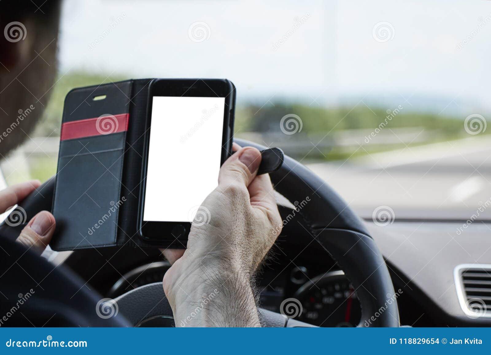 Primo piano di un uomo che conduce automobile e che tiene telefono cellulare in o anteriore