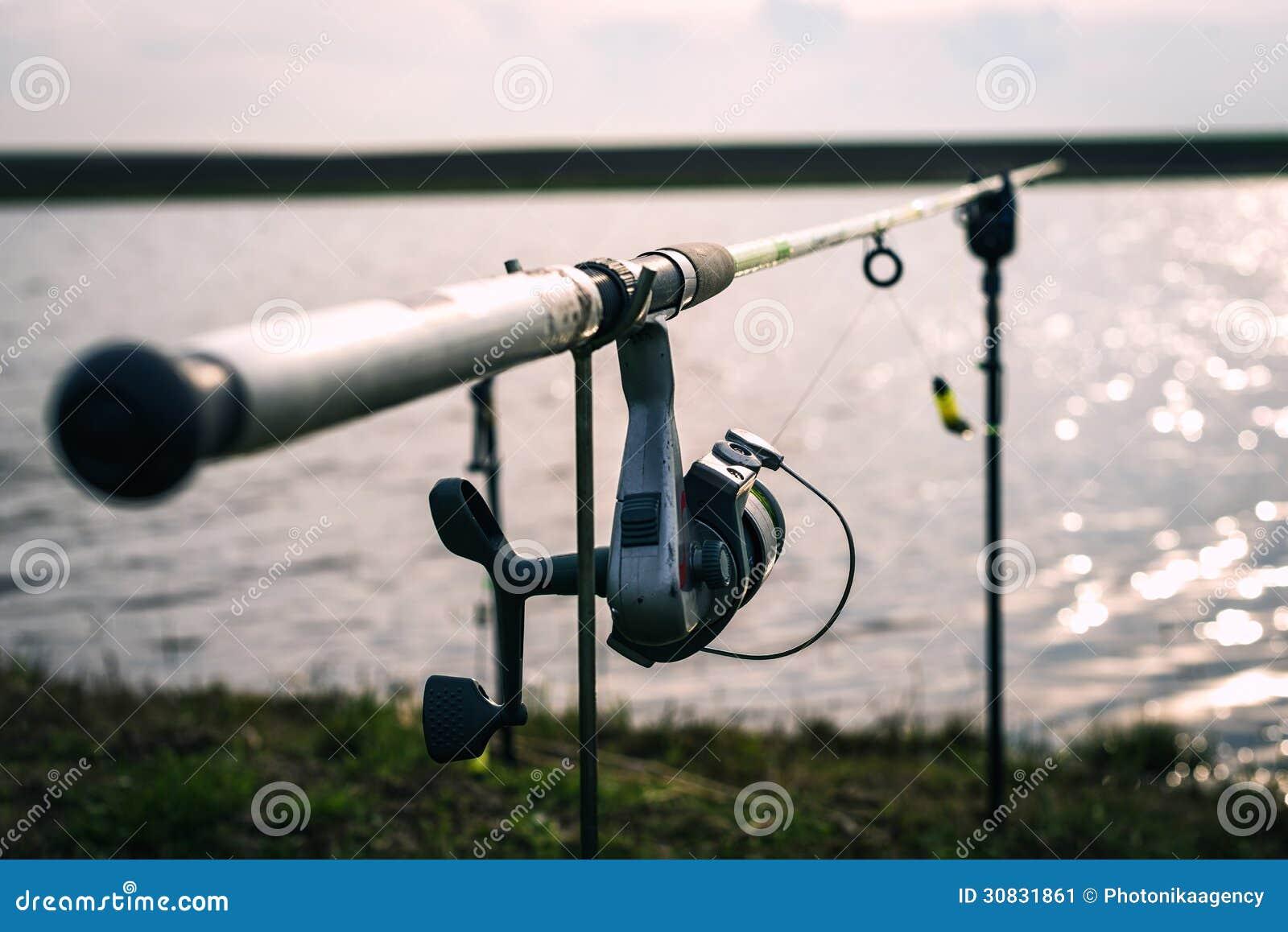 Primo piano di una bobina di pesca su una barretta vicino ad un lago