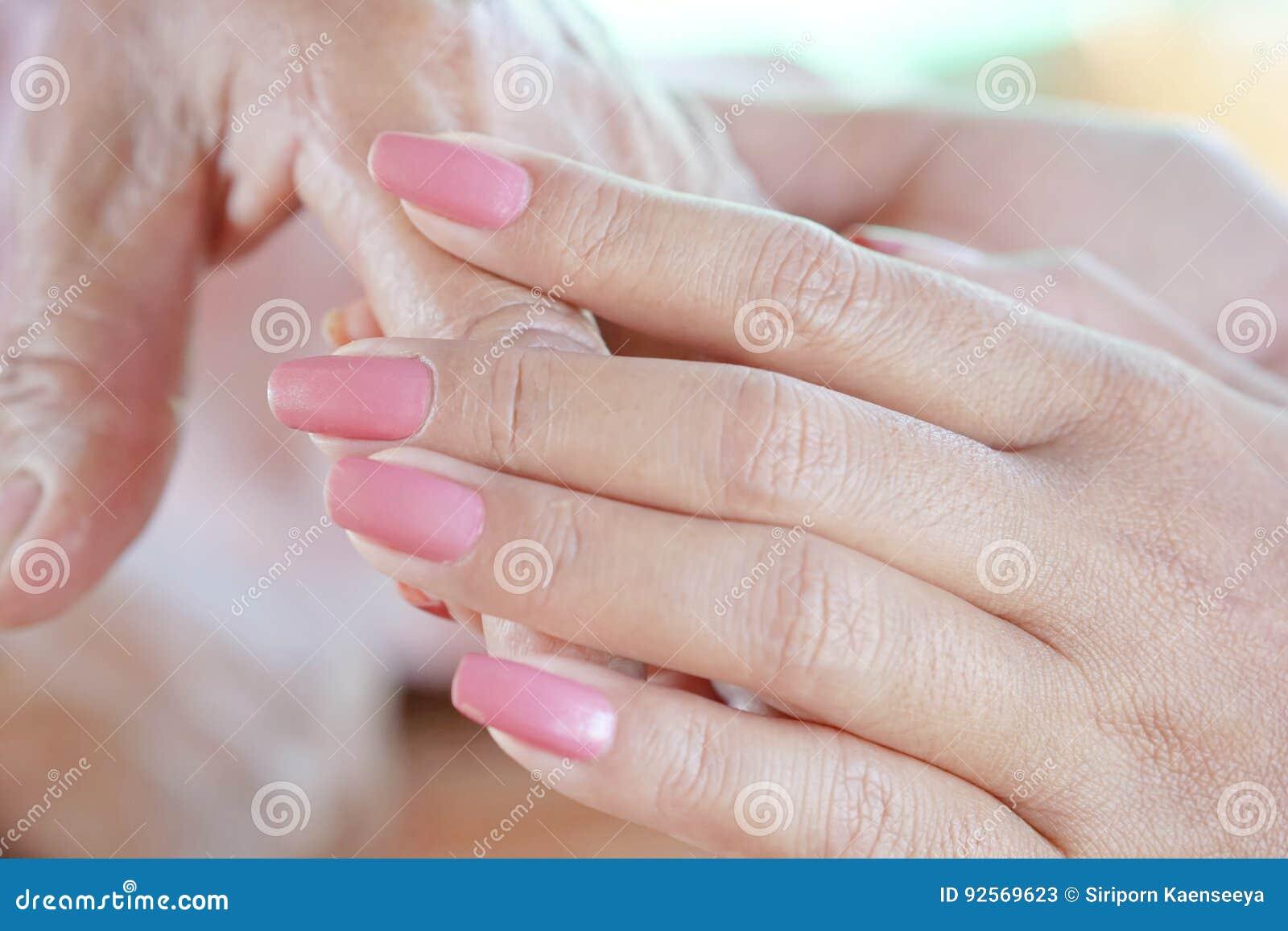 Primo piano di una donna che tiene una mano anziana del ` s della donna
