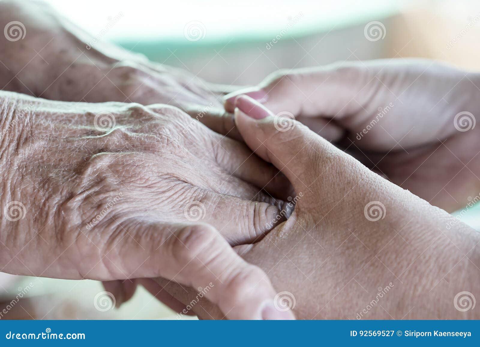 Primo piano di una figlia che tiene la sua mano del ` s della madre il giorno del ` s della madre
