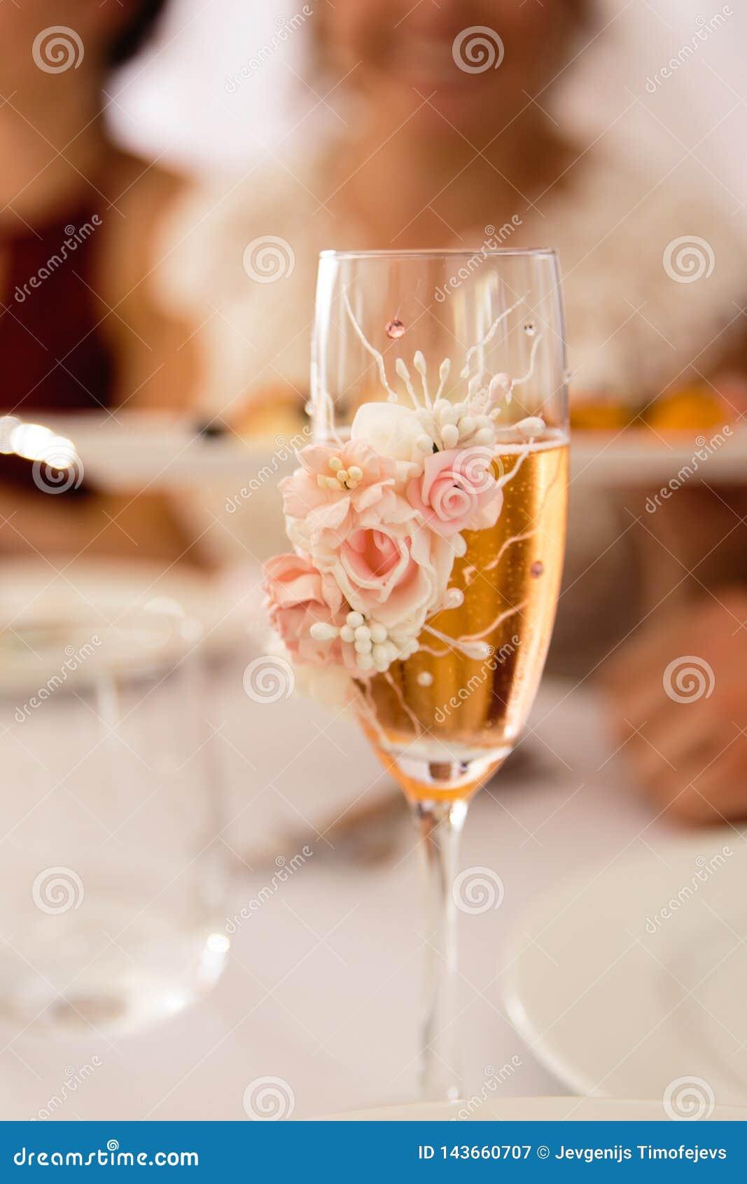 Primo piano di vetro di Champagne con la sfuocatura di profondità di campo - decorazione di messa a punto di nozze durante la ric