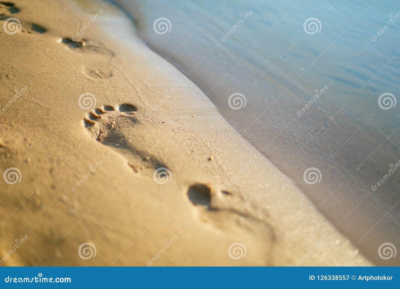 Primo piano umano di orme sulla spiaggia sabbiosa