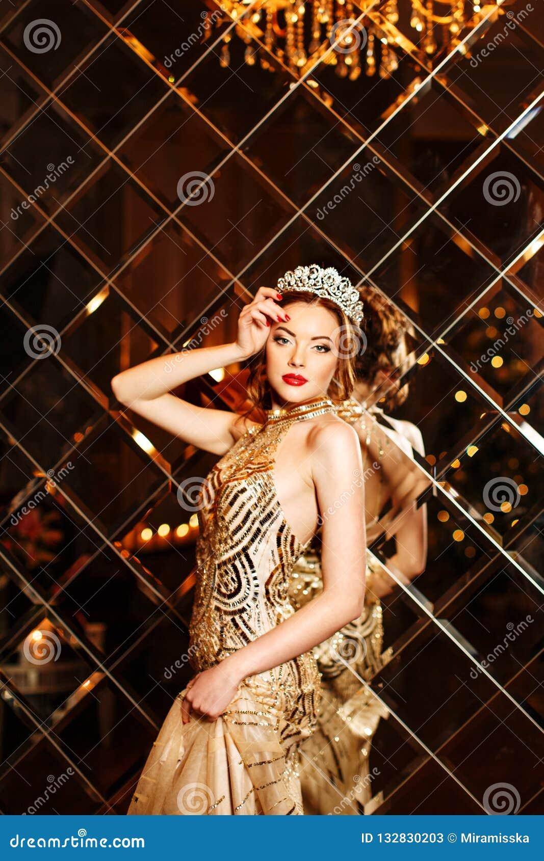 Princesa da rainha da mulher na coroa e no vestido do lux, backgr do partido das luzes