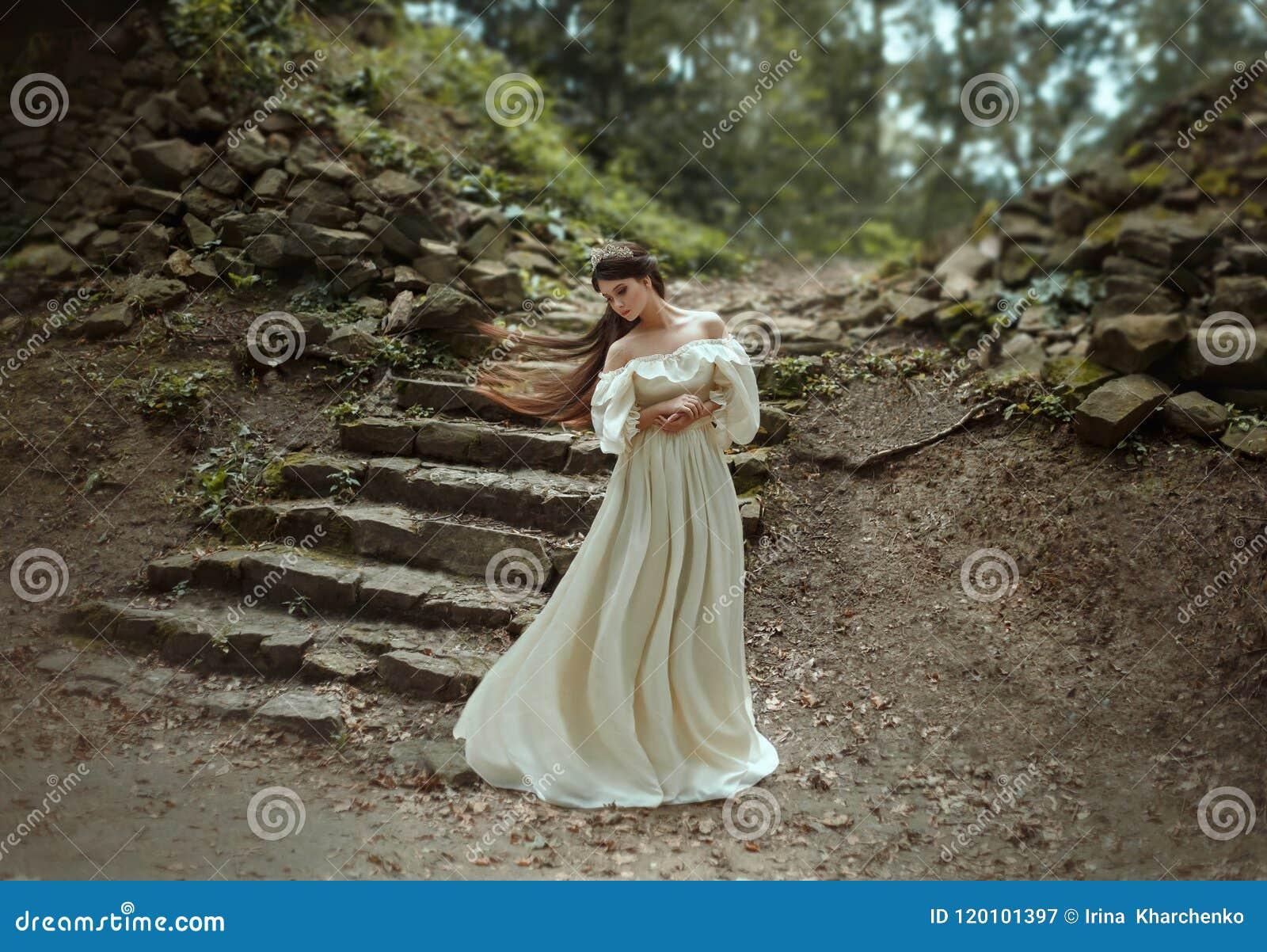 Princesa nova com o cabelo muito longo que levanta na perspectiva de uma escadaria de pedra velha A menina tem uma coroa de crist