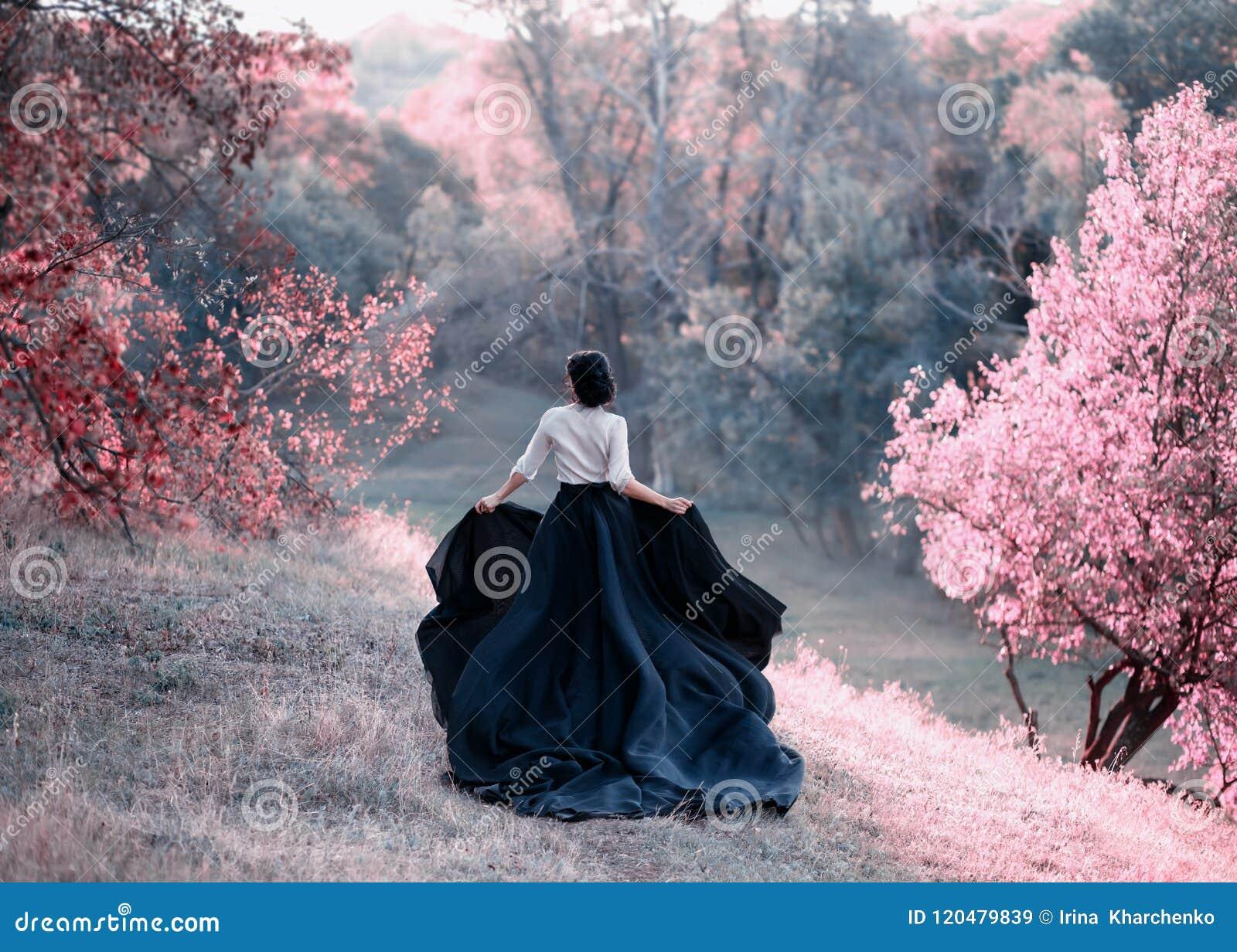 Princess w rocznik sukni ucieczkach Spacer przez malowniczych jesieni wzgórzy przy zmierzchem w różowych brzmieniach Długi pociąg