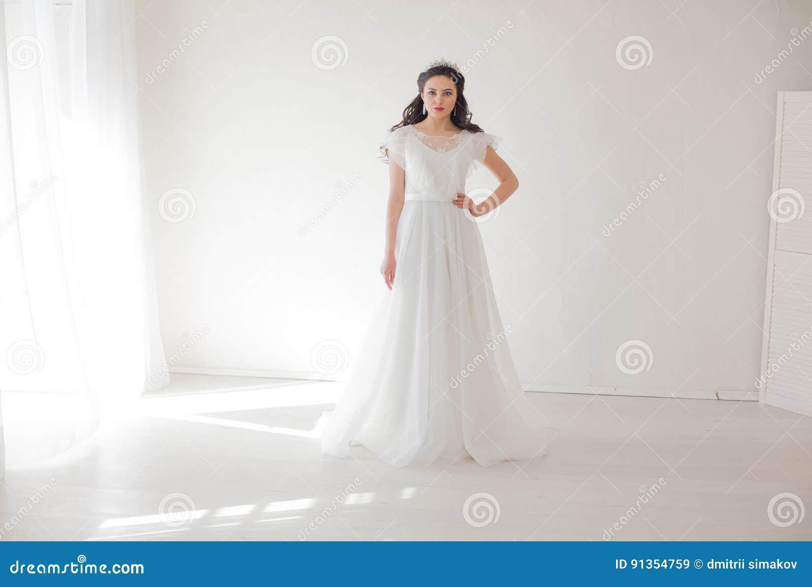 Princesse avec une couronne dans la robe blanche la jeune mariée