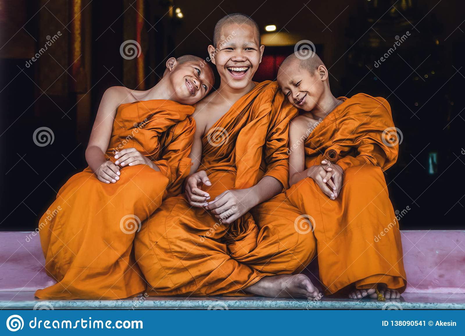 Principiantes budistas que sentam junto o sentimento feliz e o sorriso