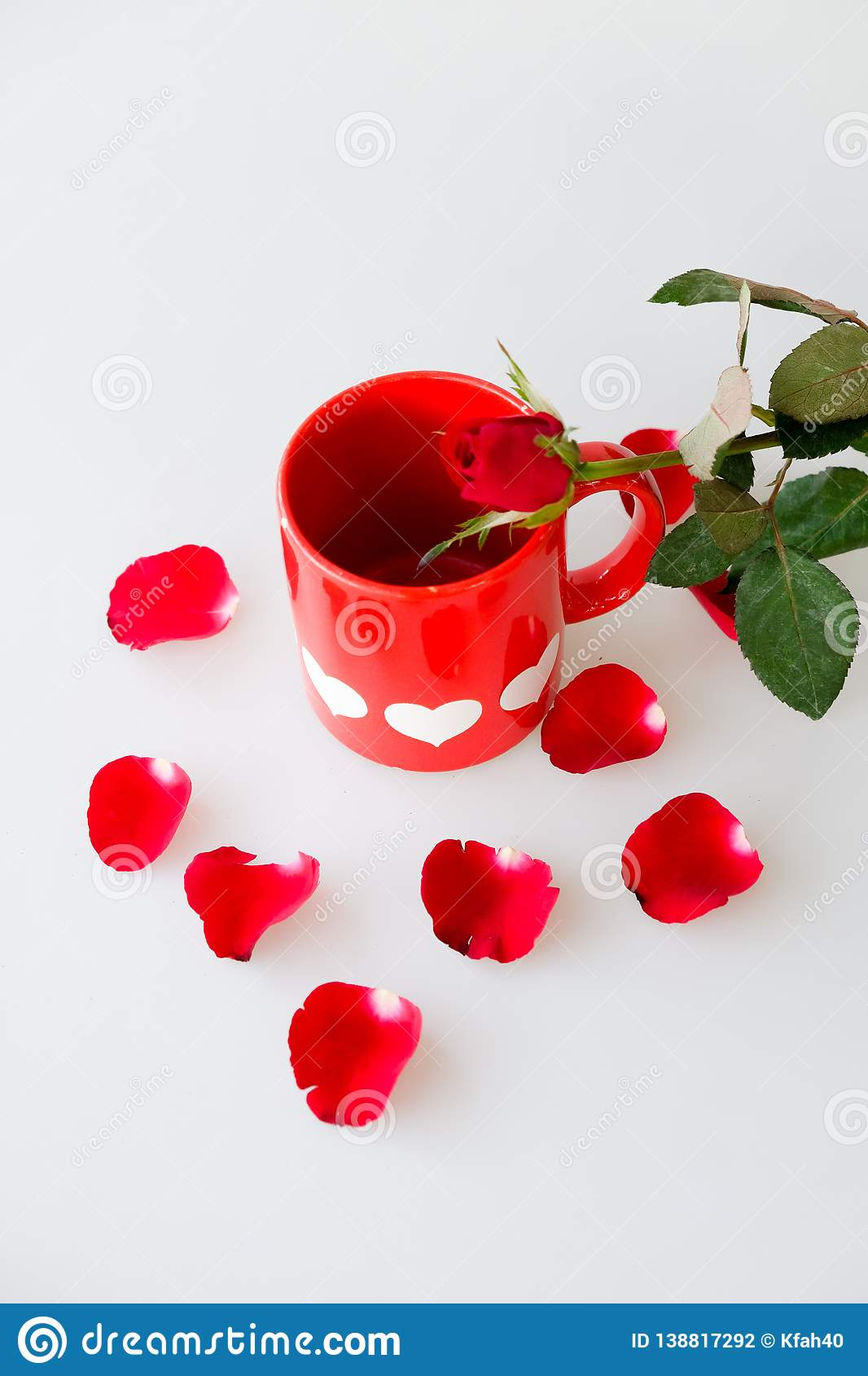Printed white hearts on red coffee cup and rose