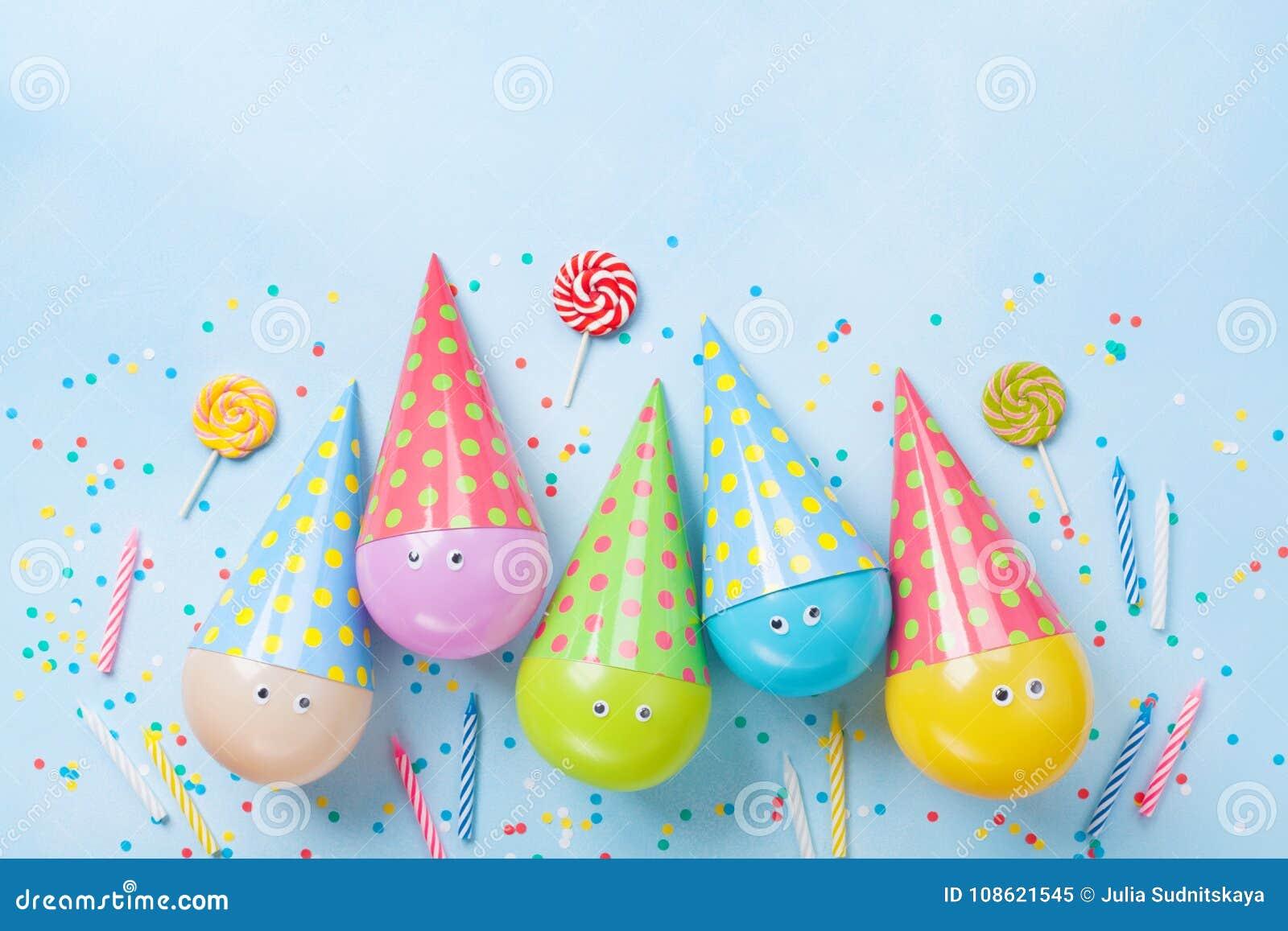 Priorità bassa del partito o di compleanno Palloni, caramella e coriandoli divertenti sulla vista blu del piano d appoggio Dispos
