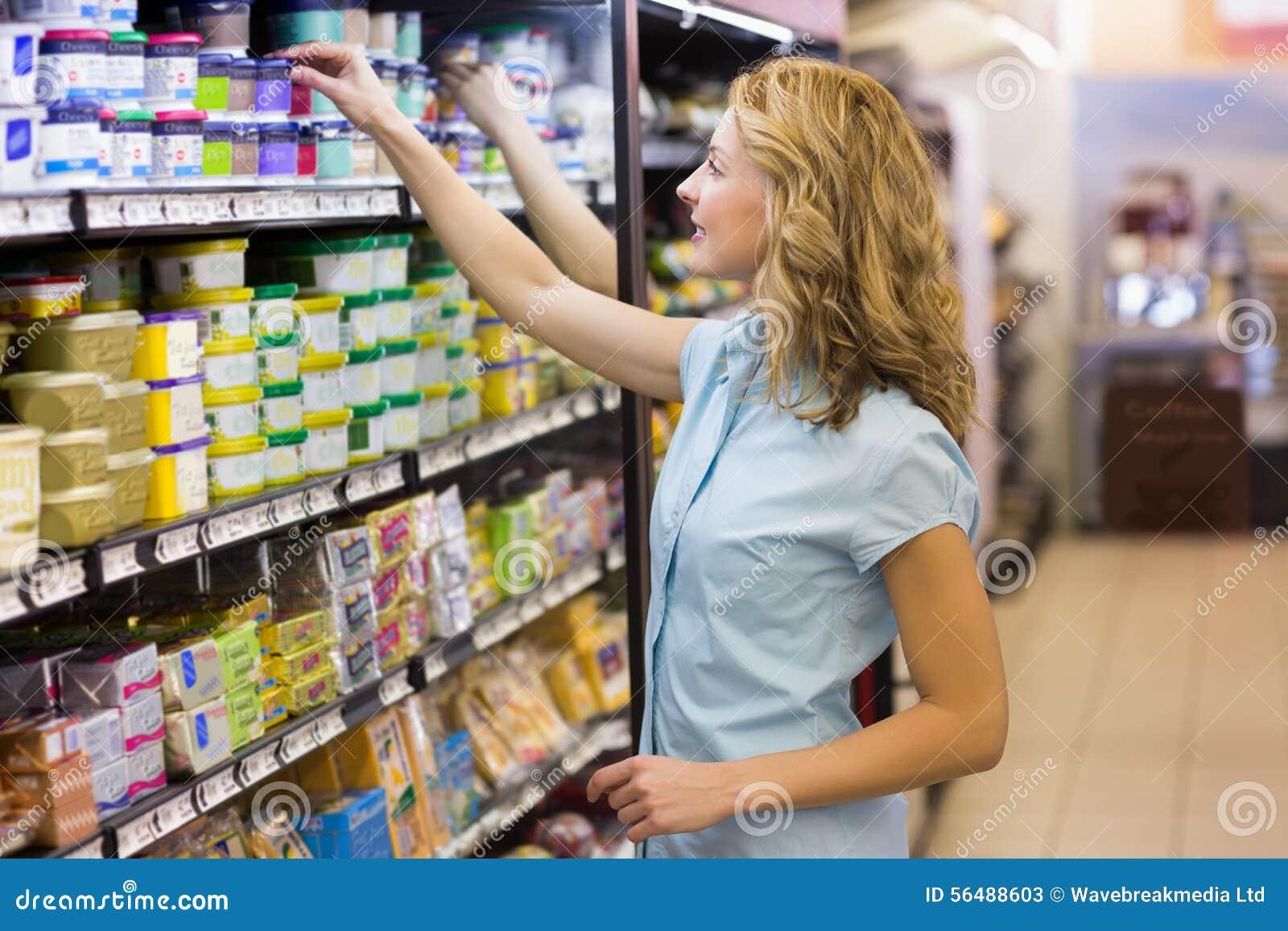 Prise assez blonde de femme produits dans les étagères