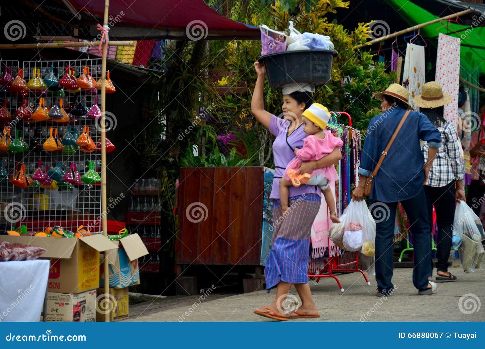 Prise birmanne de mère le bébé et le plastique de transport de bassin sur son h