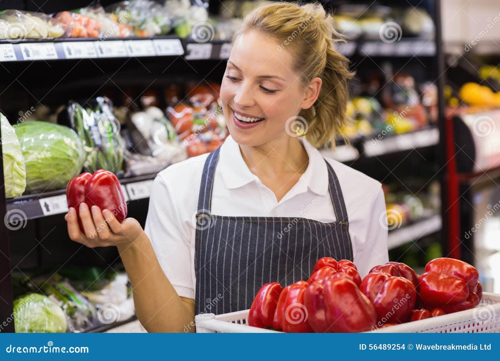 Prise blonde de sourire de travailleur légumes