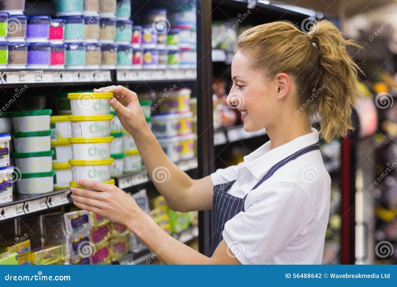 Prise blonde de sourire de travailleur produits dans l étagère