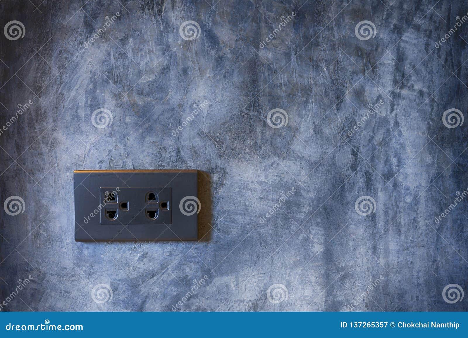 Prise de courant noir avec le fond de mur de ciment