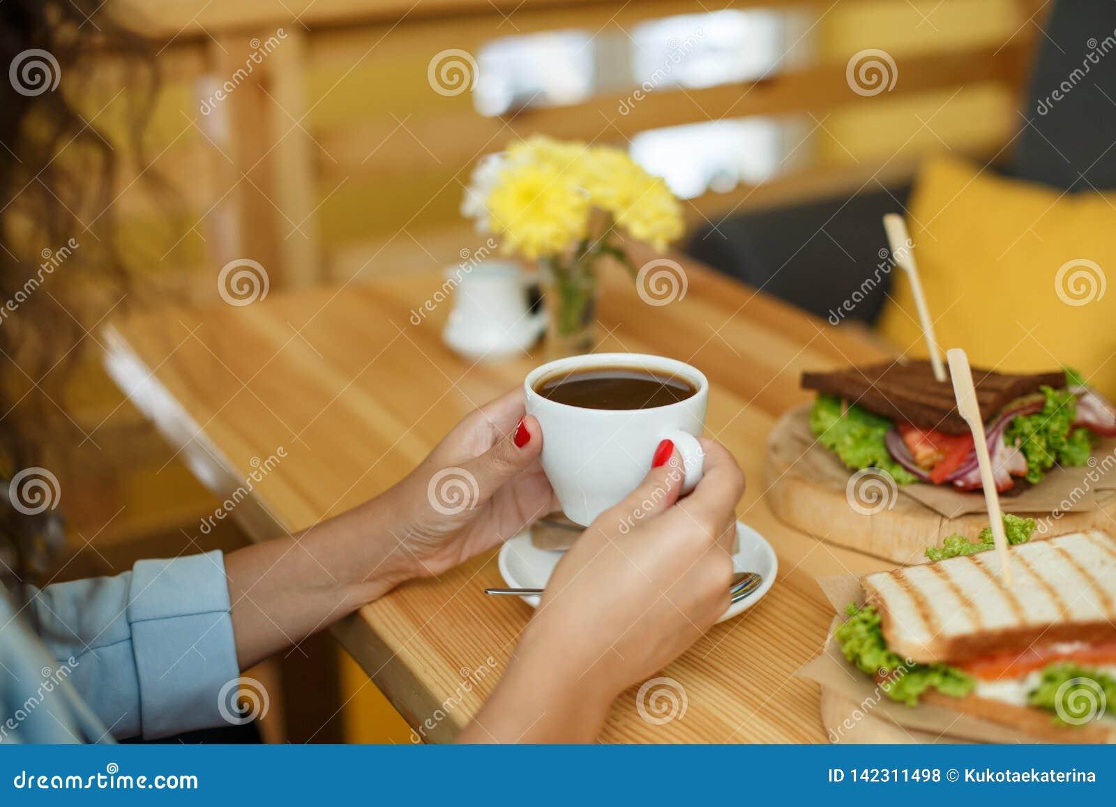 Prise de femme par tasse de café à la table en bois de backgroud, sur laquelle mensonges un sandwich