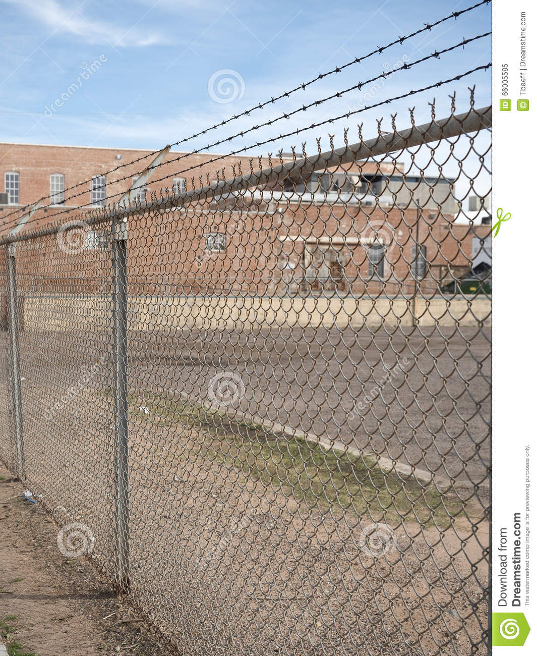 Prison barb wire wall and building stock photo
