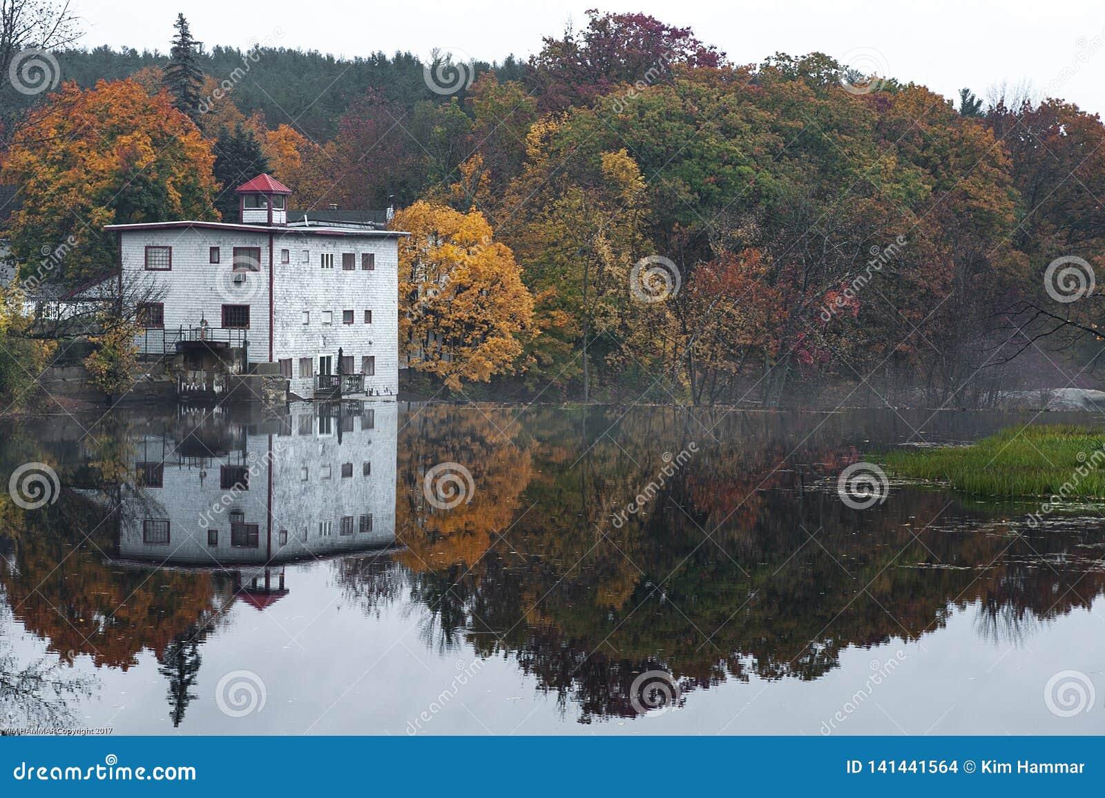 A lake reflects fall foliage on a misty morning.