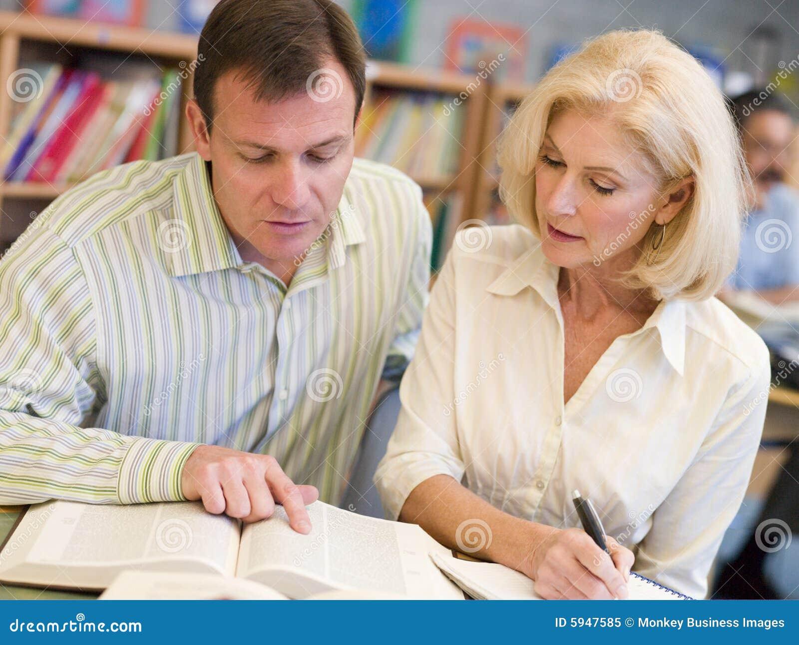 Privé-leraar die rijpe student bijstaat in bibliotheek
