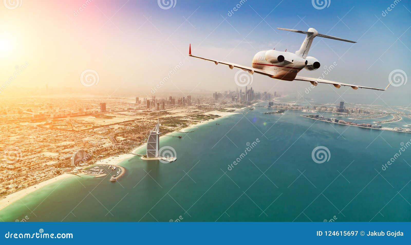 Privat jetflyg ovanför den Dubai staden i härlig solnedgångli