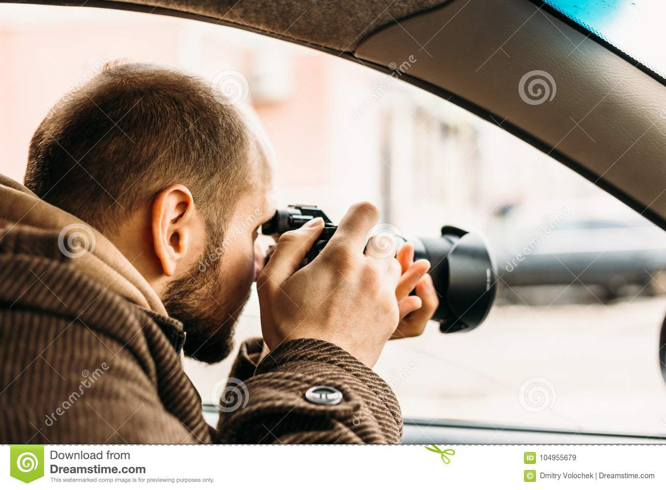 Private detective or reporter or paparazzi sitting in car and taking photo with professional camera