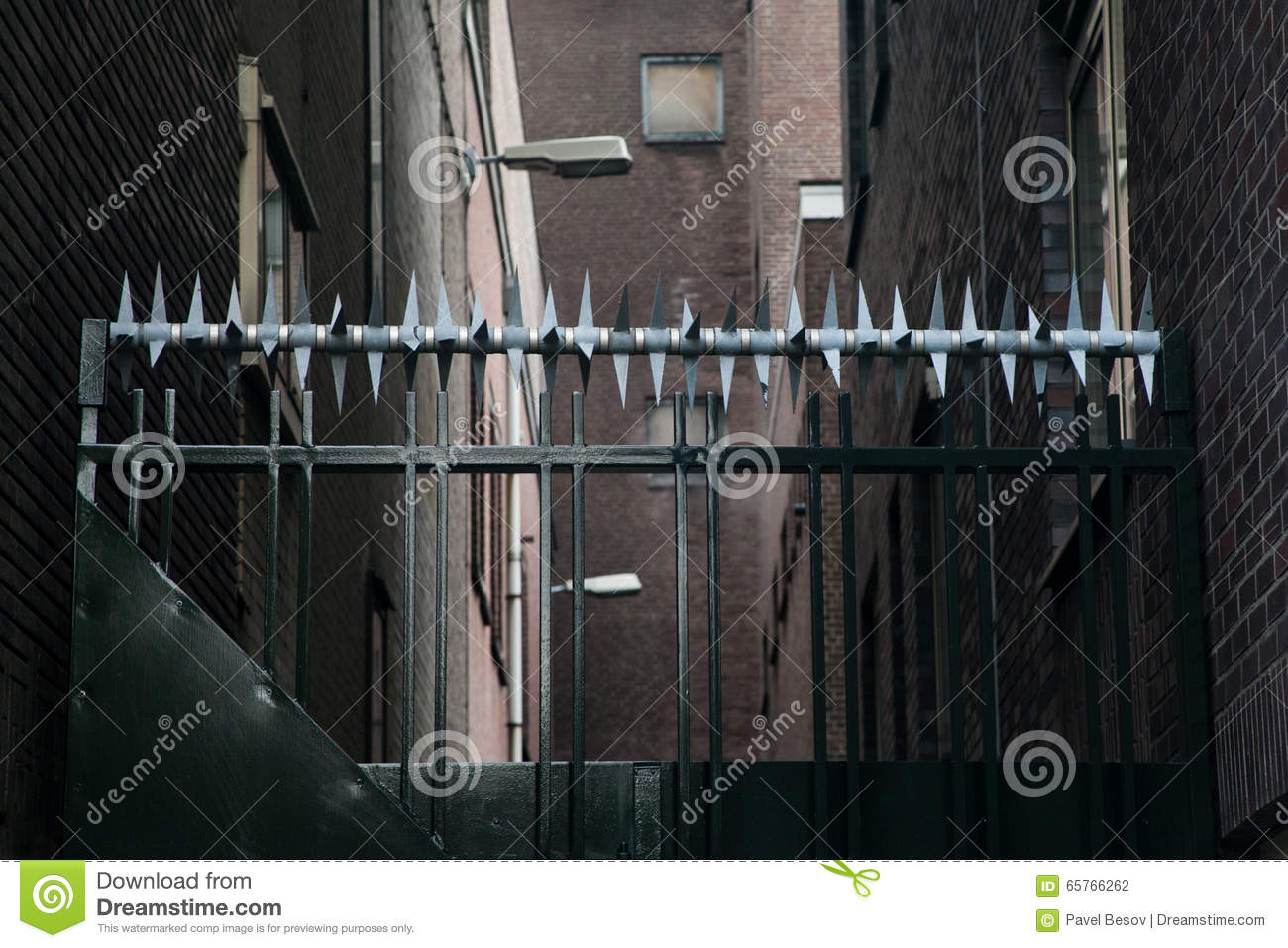 Private property, fence area. black metal gate with barbed protection. Aged paper textured background, retro colors