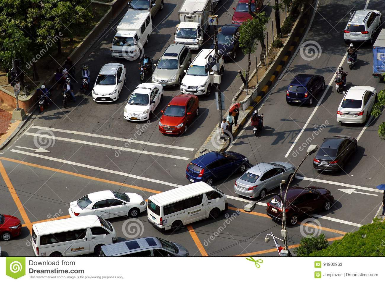 Private and public vehicles at an intersection in Pasig City, Philippines during the rush hour in the morning.