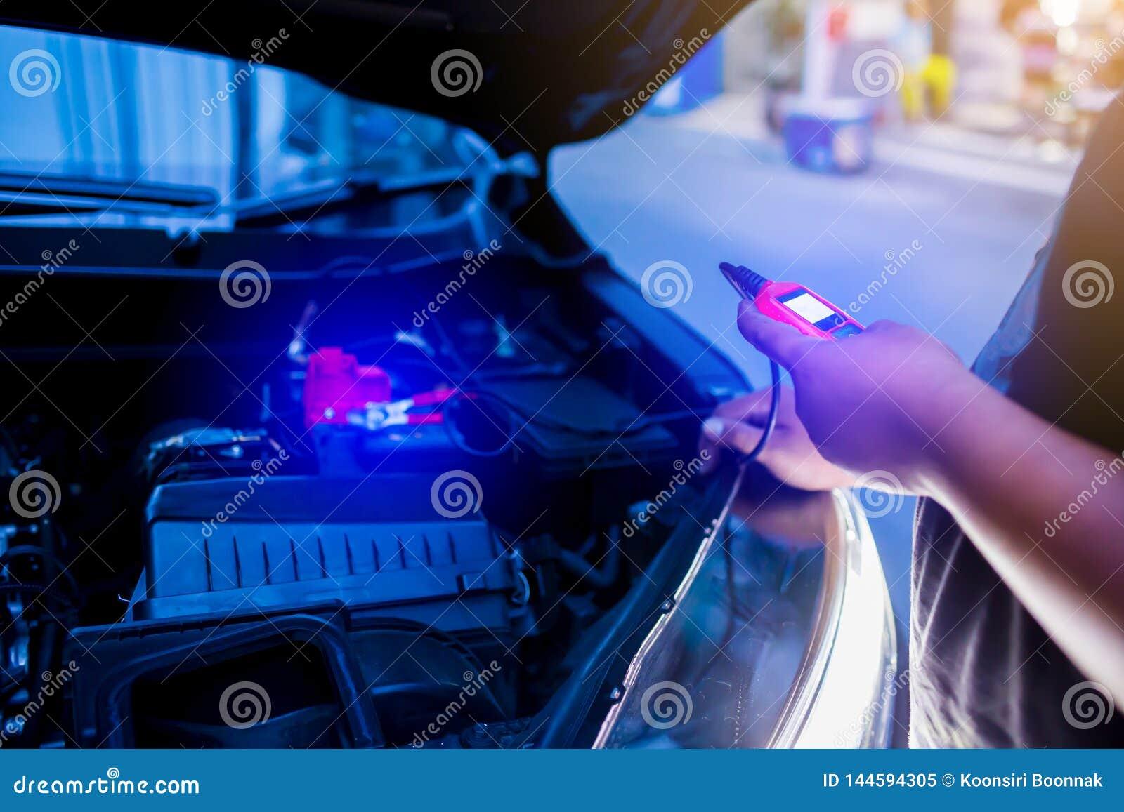 Probador masculino de la batería de la tenencia del mecánico después de cambiar la batería de coche
