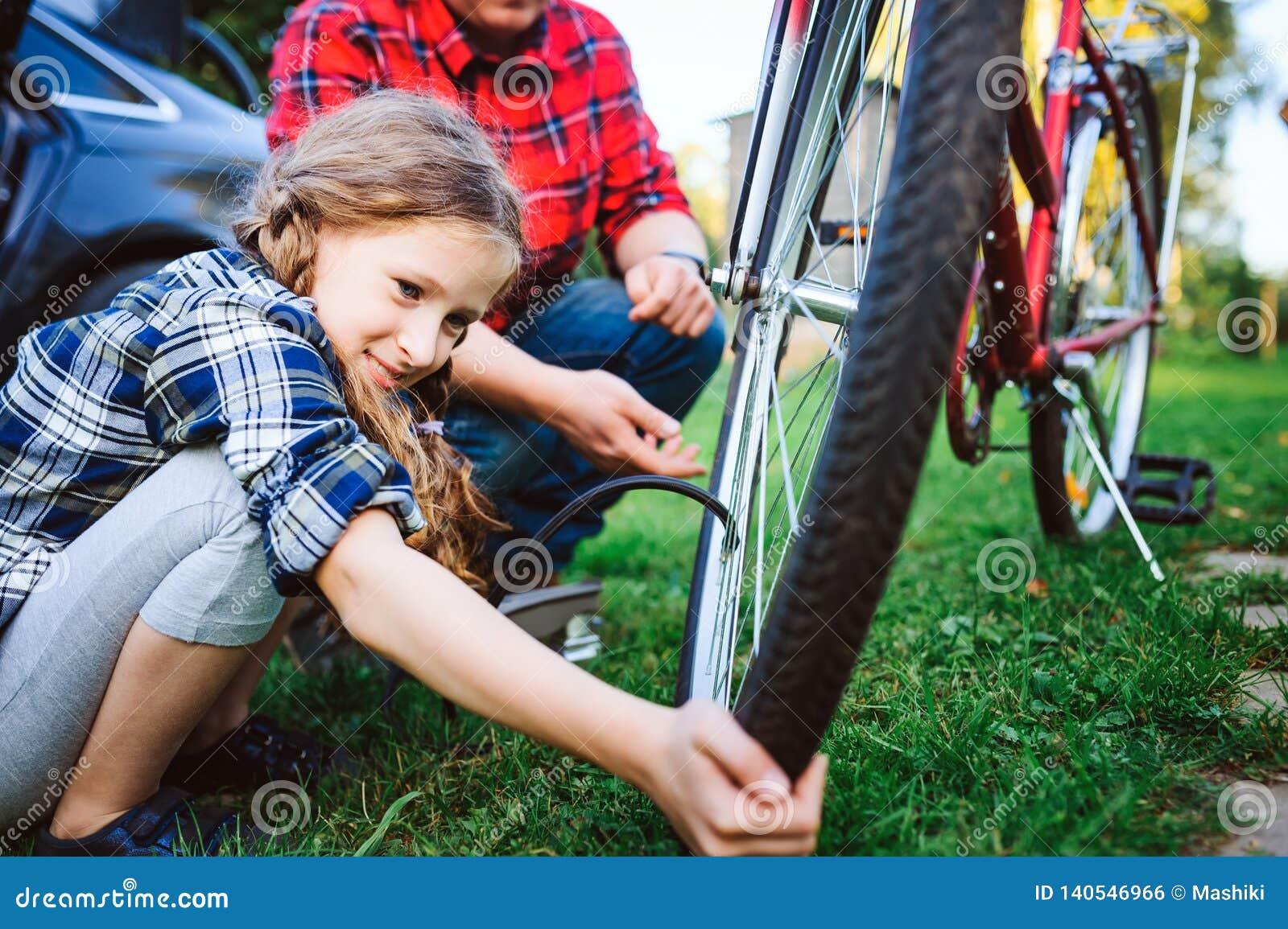 Problèmes de fixation de père et de fille avec la bicyclette extérieure en été