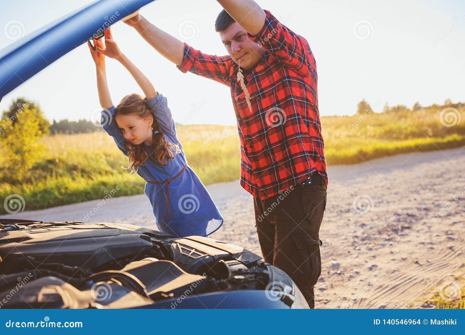 Problèmes de fixation de père et de fille avec la voiture pendant le voyage par la route d été