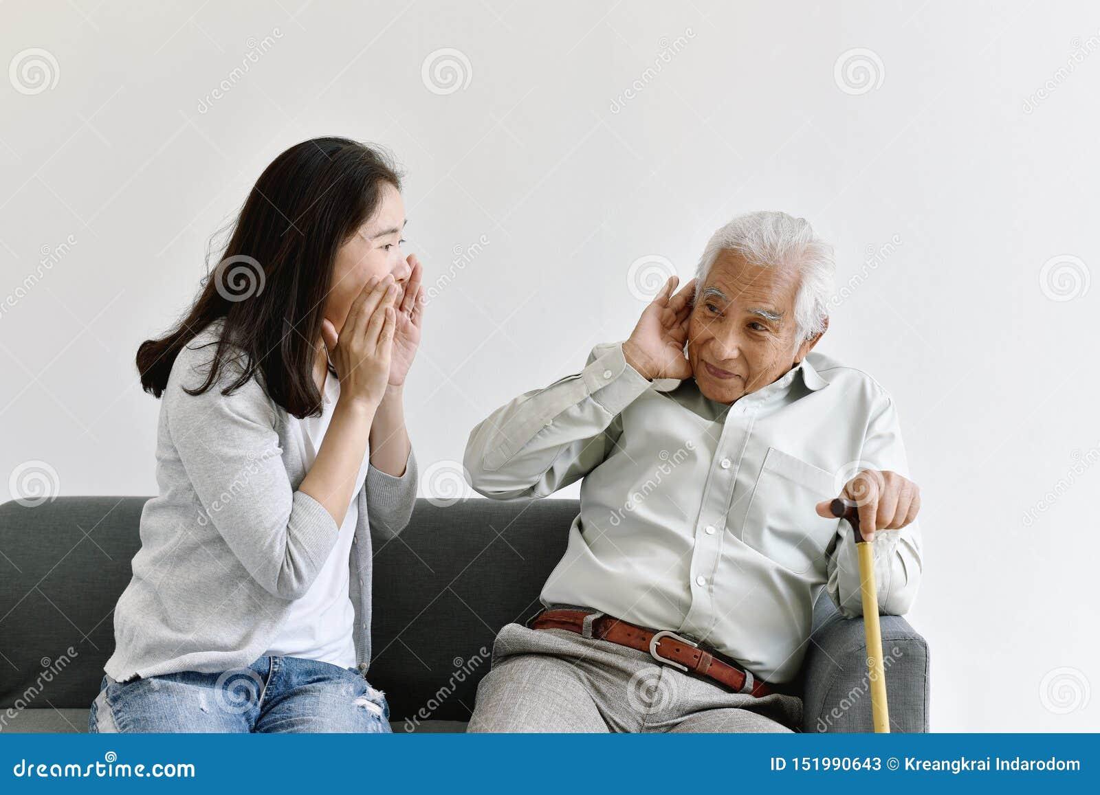 Problema de la pérdida de oído, viejo hombre asiático con la mano en el gesto del oído que intenta escuchar mujer de grito