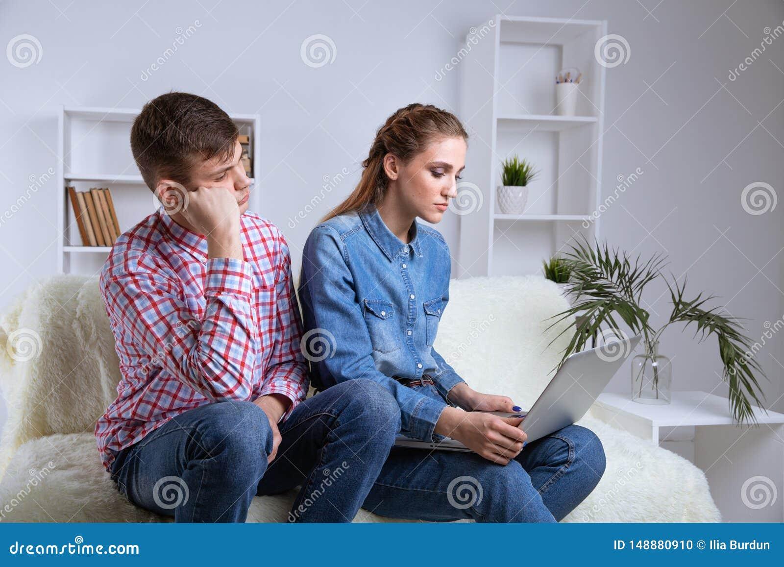 Problema nelle coppie Uomo turbato che si siede su un sof? vicino al suo computer portatile di sorveglianza della donna