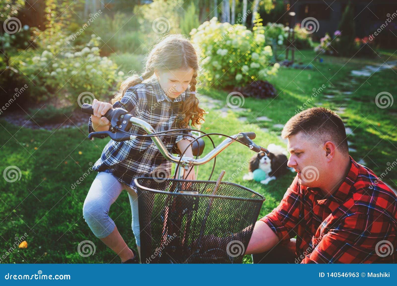 Problemas da fixação do pai e da filha com a bicicleta exterior no verão