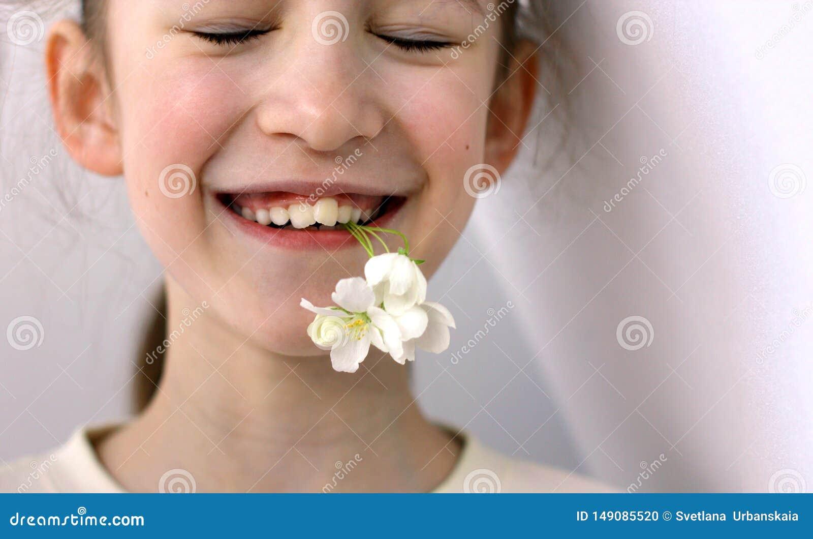 Problematische tanden in een jong mooi meisje De reden van de krommerij om de tandarts en orthodontist te bezoeken