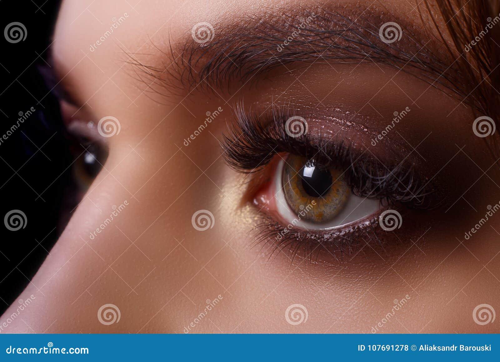 Procedura di estensione del ciglio Occhio della donna con i cigli lunghi dopo la procedura di estensione Cigli bianchi Fondo scur